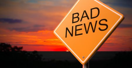 bad news on a road sign showing fear center of the brain controlling our investment decisions